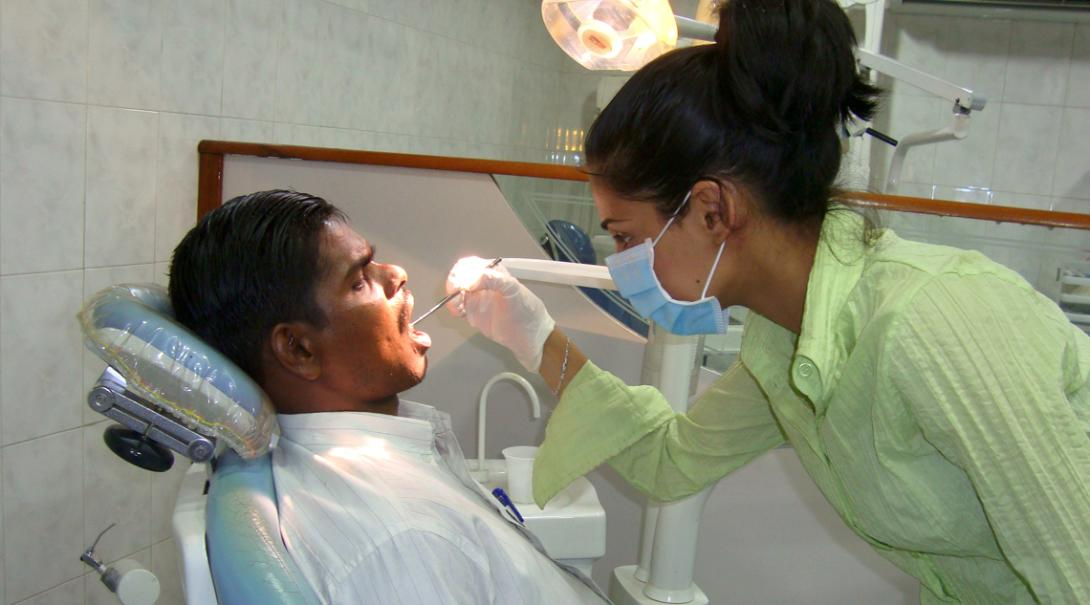 A local dentist performs a procedure on a patient in India.